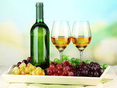 Ripe grapes, bottle and glasses of wine on tray, on bright background — Foto Stock