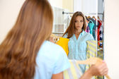 Beautiful girl choose blouses near mirror on room background — Stock Photo