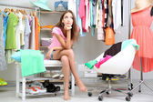 Beautiful girl thinking what to dress in walk-in closet — Stock Photo