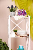 Beautiful white shelves with tableware and decor, on color wall background — Stock Photo