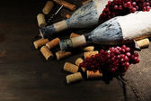 Old bottles of wine, grapes and corks on wooden background — Stock Photo
