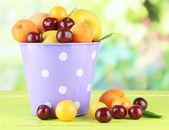 Světlé letní ovoce v vědro na dřevěný stůl na přírodní pozadí — Stock fotografie