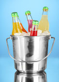 Bottles with tasty drinks in bucket with ice cubes, in bright background — Stock Photo