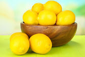 Ripe lemons in bowl on table on bright background — Stock Photo