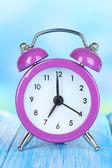 Väckarklocka på bordet på blå bakgrund — Stockfoto