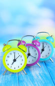 Colorful alarm clocks on table on blue background — Stock Photo