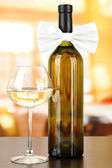 White bow tie on wine bottle on bright background — Stock Photo