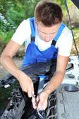 Young car mechanic repairing car engine outdoors — Stock Photo