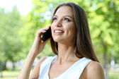 Beautiful young woman speaking on mobile phone at summer park — Stok fotoğraf