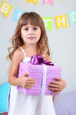 Little girl with gift in room on grey wall background — Stock Photo