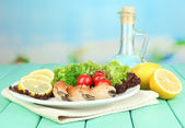Boiled crab claws on white plate with salad leaves and tomatoes,on wooden table, on bright background — Stock Photo