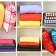 Bright pillows, towels and plaids on shelves, isolated on white — Stock Photo #30518233