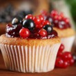 Tasty muffins with berries on wooden table — Stock Photo #30518389