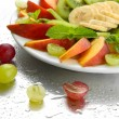 Assortment of sliced fruits on plate with drops — Stock Photo