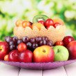 Stock Photo: Assortment of juicy fruits on wooden table, on bright background