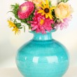 Beautiful bouquet of bright flowers in color vase, on wooden table, on bright background — Stock Photo