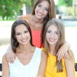 Three beautiful young woman  sitting on bench in summer park — Stock Photo