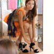 Beautiful girl trying shoes near mirror on room background — Stock Photo