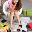 Beautiful girl chooses shoes in room — Stock Photo #30519607