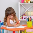 Little girl draws sitting at table in room on grey wall background — Stock Photo