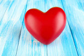 Decorative red heart on color wooden background — Stock Photo