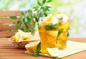 Ledový čaj s citronem a mátou na dřevěný stůl, venku — Stock fotografie