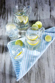 Glass pitchers of water and glasses on wooden table close-up — Stock Photo