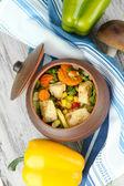 Pečené smíšené zeleniny s kuřecími prsíčky v hrnci, na dřevěné pozadí — Stock fotografie