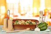 Cazuela con verduras y carne, en mesa de madera, sobre fondo brillante — Foto de Stock