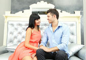 Beautiful young romantic couple sitting on sofa — Foto Stock