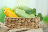 Sliced and whole raw zucchini in wicker crate, outdoors — Stock Photo