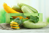 Sliced and whole raw zucchini in wooden crate, outdoors — Stock Photo