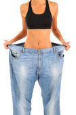 Slim girl in big jeans isolated on white — Foto Stock