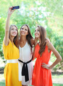 Three beautiful young woman taking picture in summer park — Stock Photo