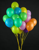 Colorful balloons on dark color background — Stock Photo