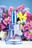 Women perfume in beautiful bottle and flowers on blue background — Stock Photo