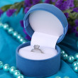 Stock Photo: Flowers and engagement ring on blue cloth