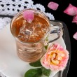 Glass cup of ice tea from tea rose on metallic tray on napkin on black background — Stock Photo