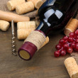 Stock Photo: Bottle of wine, grapes and corks on wooden background