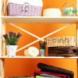 Beautiful white shelves with different home related objects, on color wall background — Stock Photo #30521059