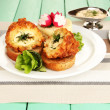 Chicken Kiev on croutons with mashed potatoes, on wooden table, on bright background — Stock Photo #30521575