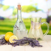 Lavender lemonade in bottle and jug, on bright background — Stock Photo