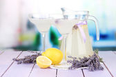 Lavender lemonade in glass jug and cocktail glasses, on bright background — Stock Photo