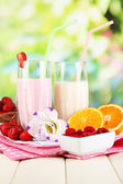 Delicious milk shakes with strawberries and orange on wooden table on natural background — Stock Photo