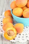 Frische natürliche aprikose in schüssel auf grüne holztisch — Stockfoto