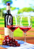 Glasses of wine on napkin on wooden table on nature background — Stock Photo
