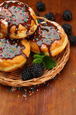 Tasty donuts with chocolate and berries on wooden table — Stock Photo