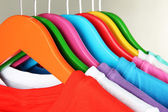 Different shirts on colorful hangers on grey background — Stock Photo
