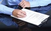 Businessman writing on document in office close-up — Stock fotografie