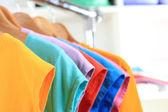 Variedade de casual camisetas em cabides de madeira no fundo de prateleiras — Fotografia Stock